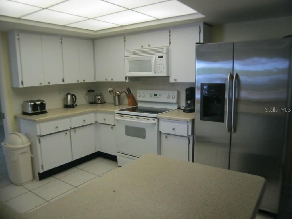 The kitchen is positioned between the living room and great room with a large pass-through window to the breakfast room with views of the pool and creek. - Single Family Home for sale at 450 Coral Creek Dr, Placida, FL 33946 - MLS Number is D5901346