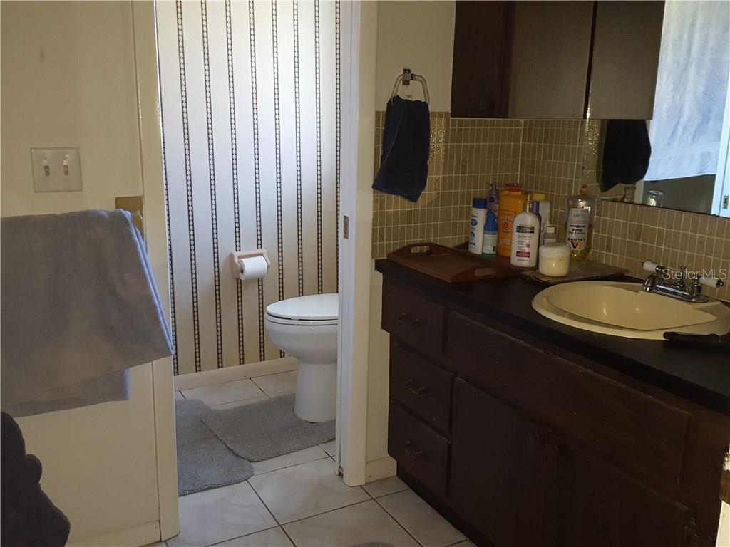 The master bath has a shower stall across from the toilet and a large walk-in closet just to the left of this picture, across from the vanity. - Single Family Home for sale at 360 E Wentworth Cir, Englewood, FL 34223 - MLS Number is D5921470