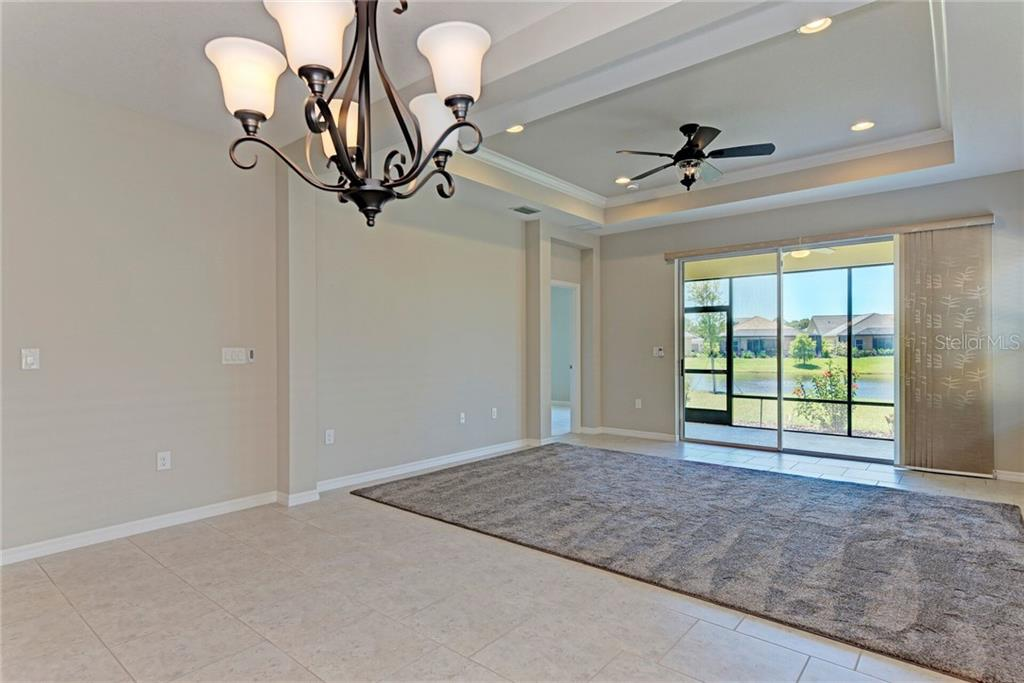 Tray ceiling with crown molding and a brand new rug for your family room. - Single Family Home for sale at 141 Avens Dr, Nokomis, FL 34275 - MLS Number is D6100104