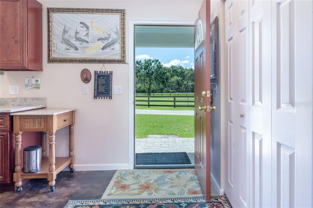 Entry to the dwelling unit under a covered porch with ample room to sit - Single Family Home for sale at 7339 Hawkins Rd, Sarasota, FL 34241 - MLS Number is D6102762