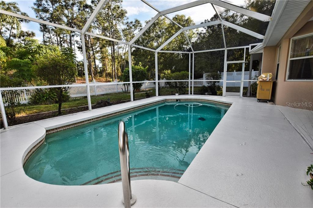 Pool overlooking backyard.  Screened enclosure. - Single Family Home for sale at 8 Medalist Cir, Rotonda West, FL 33947 - MLS Number is D6104474
