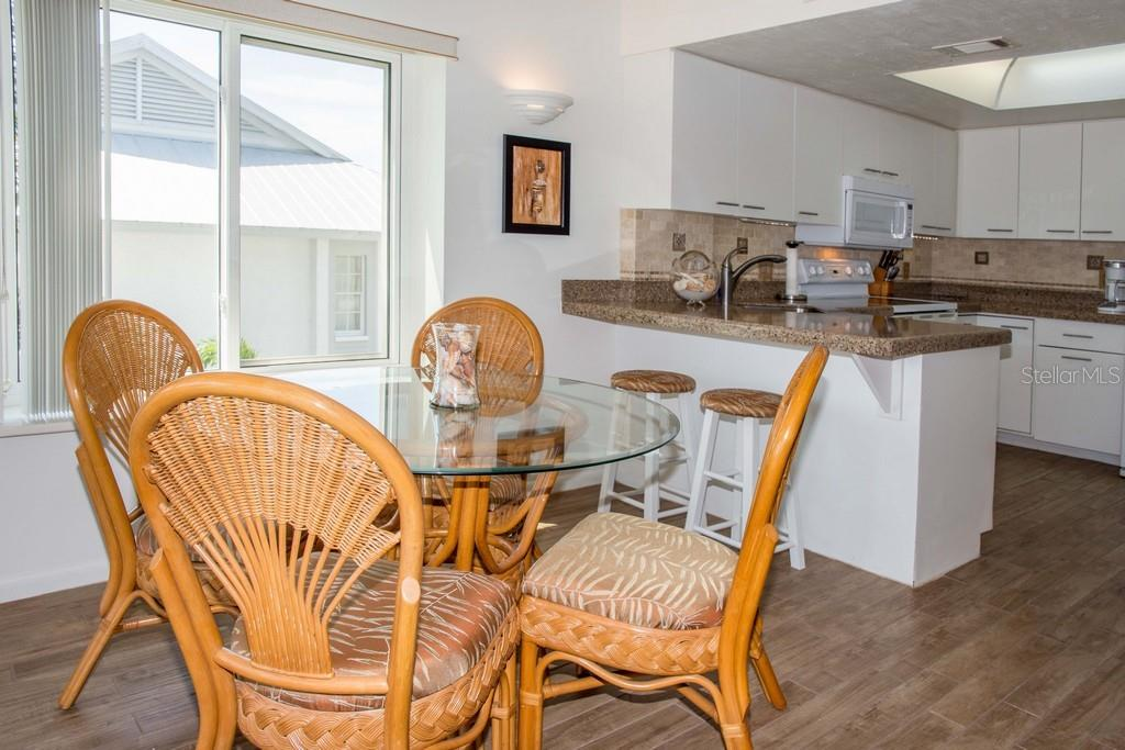 View of the dining room and kitchen. - Condo for sale at 7070 Placida Rd #1223, Placida, FL 33946 - MLS Number is D6108523