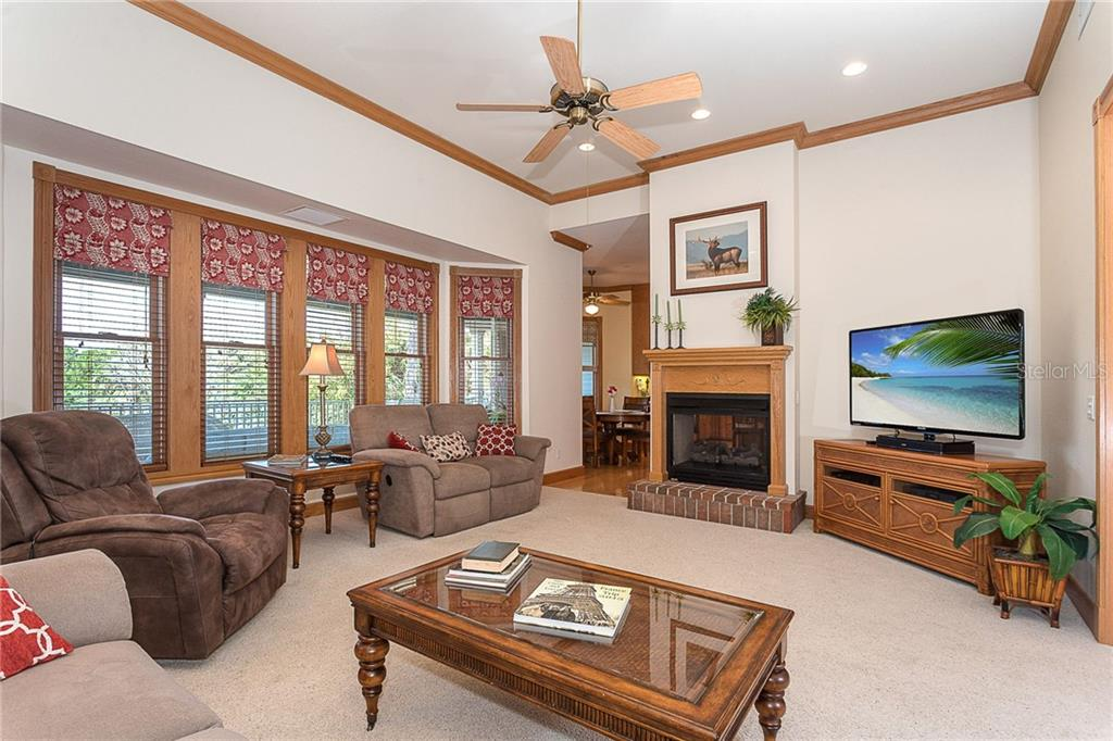 Living room with volume ceilings, beautiful crown molding and custom wood hearth on the double-sided gas fireplace. - Single Family Home for sale at 550 S Oxford Dr, Englewood, FL 34223 - MLS Number is D6111512