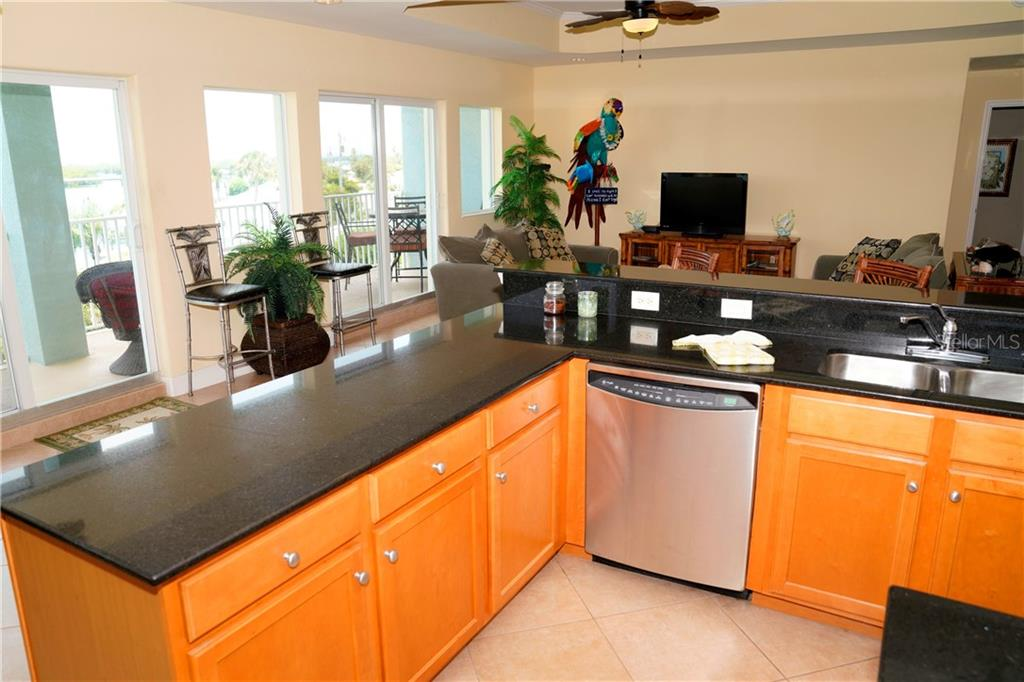 Another view of kitchen -- wood cabinetry and granite countertops. - Condo for sale at 2245 N Beach Rd #304, Englewood, FL 34223 - MLS Number is D6112346