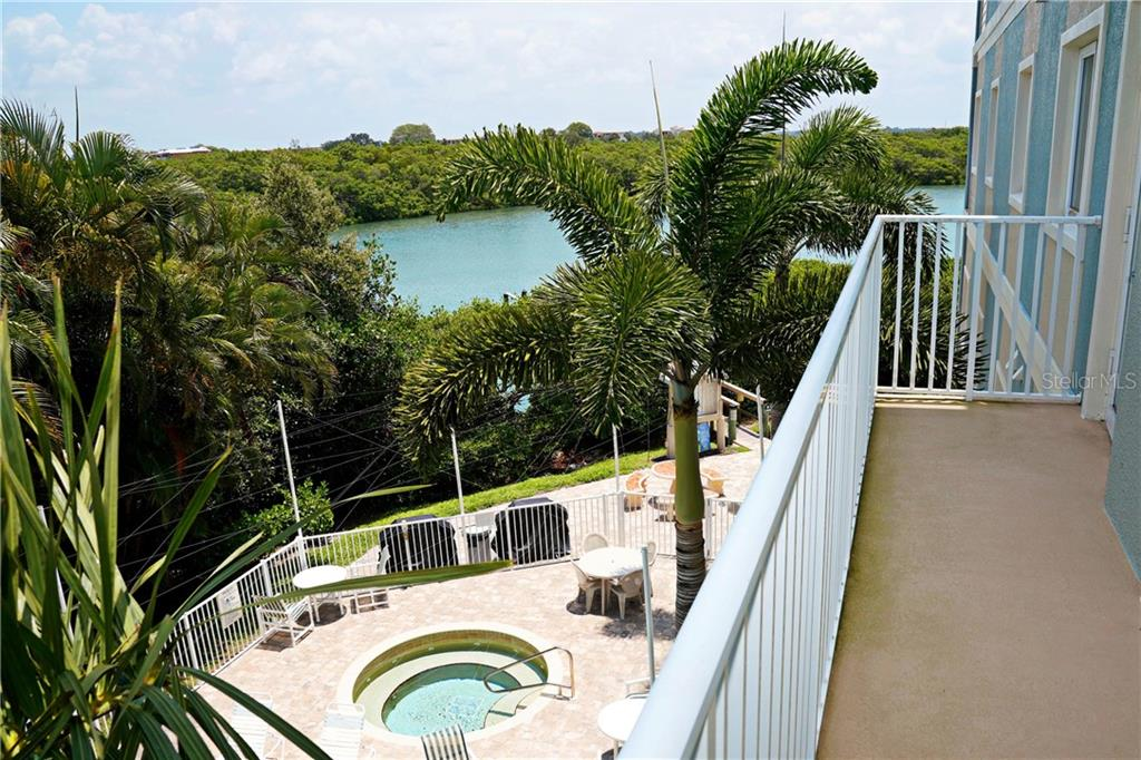 View from 2nd bedroom off the balcony.  Pool & hot tub below and water view. - Condo for sale at 2245 N Beach Rd #304, Englewood, FL 34223 - MLS Number is D6112346