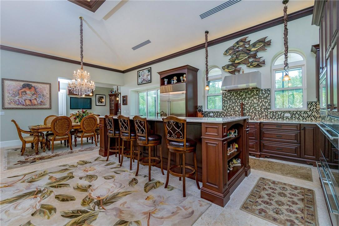 Tall rich wood cabinetry and unique tiled backsplash complimented by top of the line Wolf Appliances - Single Family Home for sale at 10161 Eagle Preserve Dr, Englewood, FL 34224 - MLS Number is D6114216