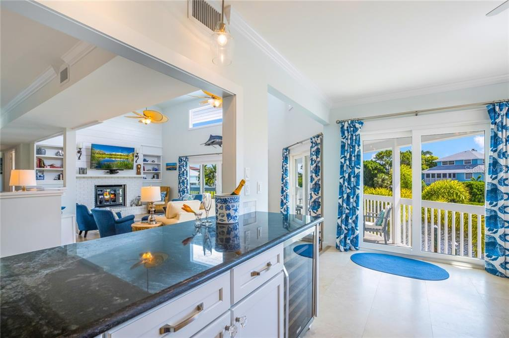 The open concept allows for conversations between the family room and kitchen, and a dual-zone wine refrigerator keeps beverages at just the right temperature - Single Family Home for sale at 511 Loquat Dr, Anna Maria, FL 34216 - MLS Number is T3196169