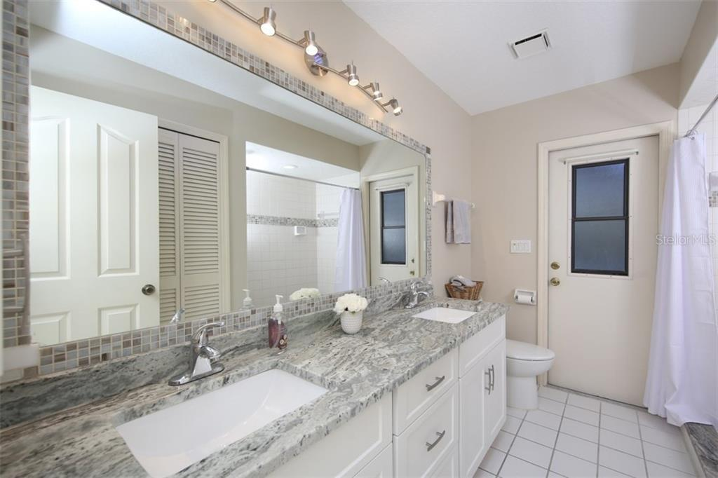 Guest pool bathroom with dual sink vanity - newly remodeled with granite counters, new flooring in shower - Single Family Home for sale at 3419 Sandpiper Dr, Punta Gorda, FL 33950 - MLS Number is C7232529