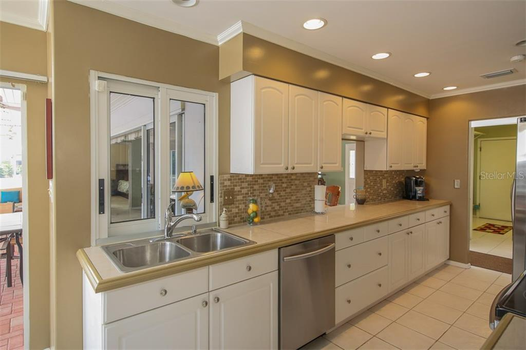 Bright Kitchen with ample cabinetry & stone countertop & tile backsplash - Single Family Home for sale at 2332 Mauritania Rd, Punta Gorda, FL 33983 - MLS Number is C7234250
