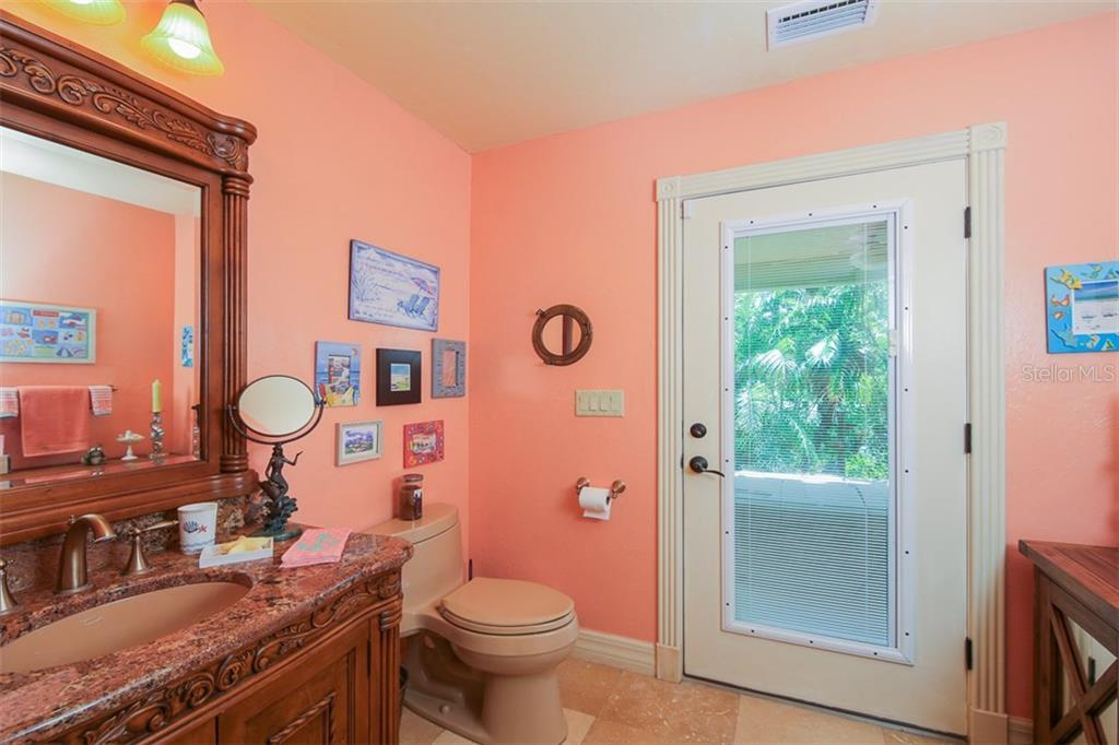 Downstairs guest/pool bathroom with wood/granite vanity, tiled walk-in shower, travertine flooring, and door to the pool & outdoors - Single Family Home for sale at 17296 Foremost Ln, Port Charlotte, FL 33948 - MLS Number is C7240998