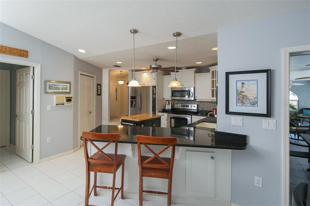 Breakfast bar seats up to 3 and opens up into the family room & kitchen nook - Single Family Home for sale at 4407 Albacore Cir, Port Charlotte, FL 33948 - MLS Number is C7245070