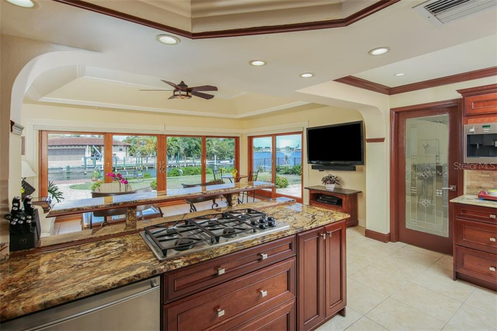 Kitchen overlooks the stunning Florida Room with wood framed impact glass sliding doors and amazing views - Single Family Home for sale at 158 Morgan Ln Se, Port Charlotte, FL 33952 - MLS Number is C7400633