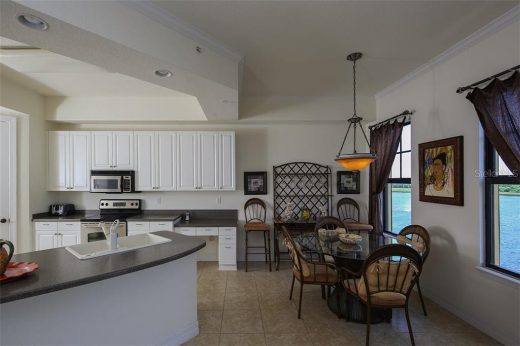 Kitchen with raised panel cabinetry and solid surface counters - Condo for sale at 95 Vivante Blvd #303, Punta Gorda, FL 33950 - MLS Number is C7402746