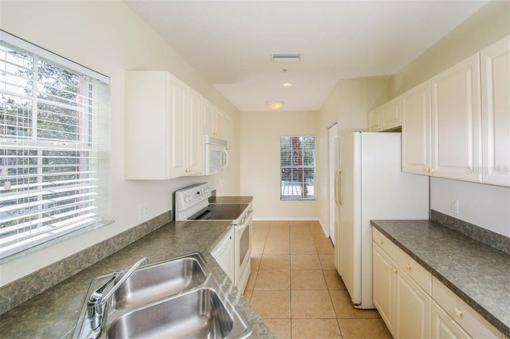 Tiled Kitchen features south facing window at stainless steel sink. - Condo for sale at 2040 Willow Hammock Cir #b208, Punta Gorda, FL 33983 - MLS Number is C7408424