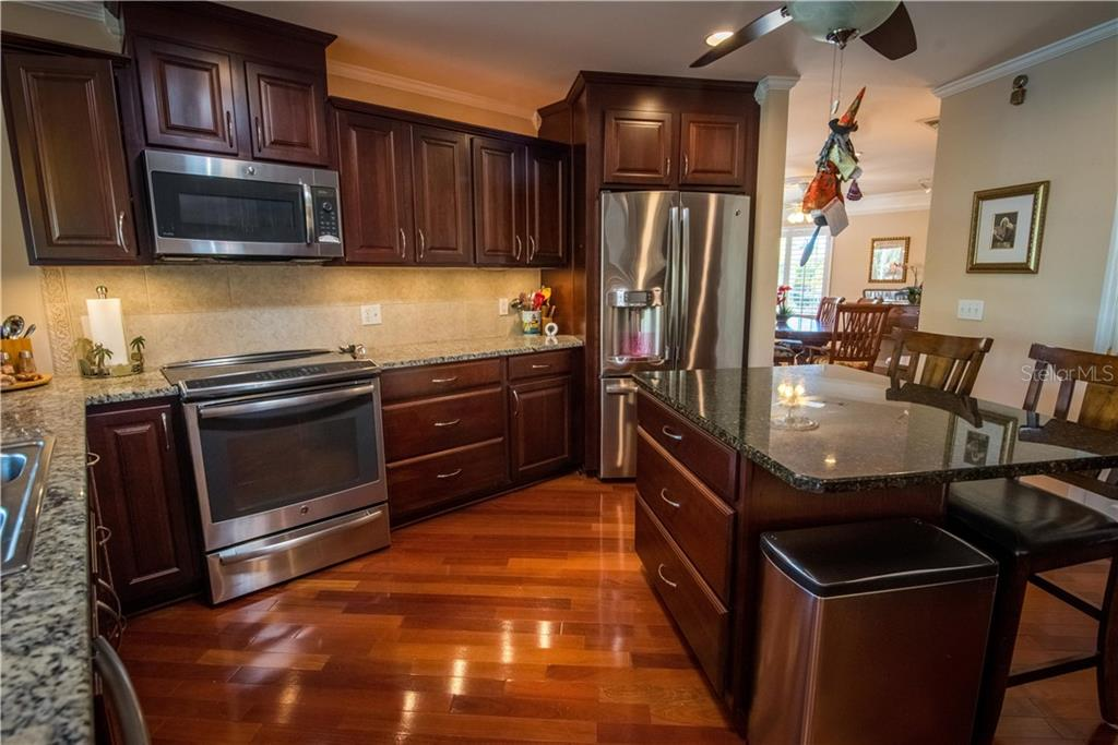 Drop-in range features convection oven. Stainless Steel appliances complement the rich wood tones of the kitchen. - Single Family Home for sale at 1440 Appian Dr, Punta Gorda, FL 33950 - MLS Number is C7425399