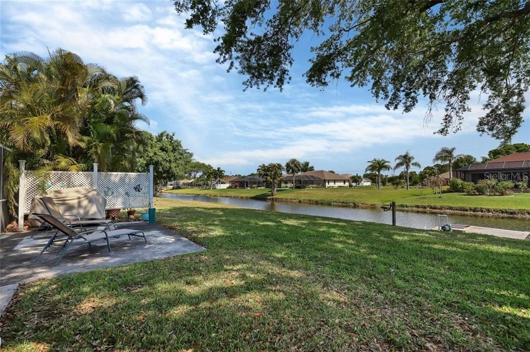 partial backyard, patio and waterfront view - Single Family Home for sale at 116 Mariner Ln, Rotonda West, FL 33947 - MLS Number is C7441260