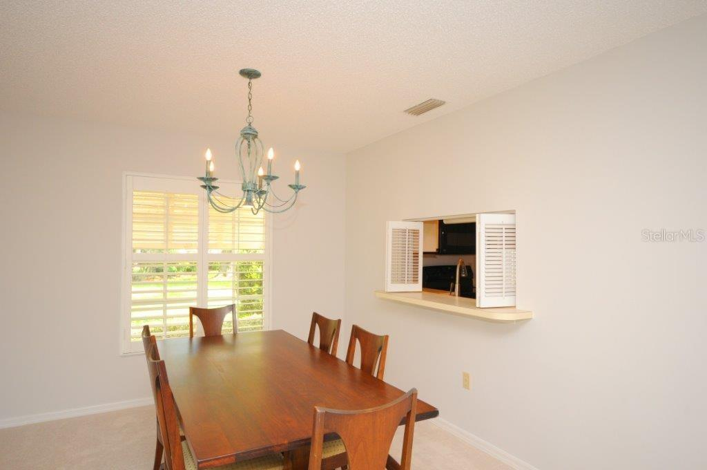 Dining area with pass-thru from kitchen - Villa for sale at 5510 Chanteclaire #46, Sarasota, FL 34235 - MLS Number is A4156527