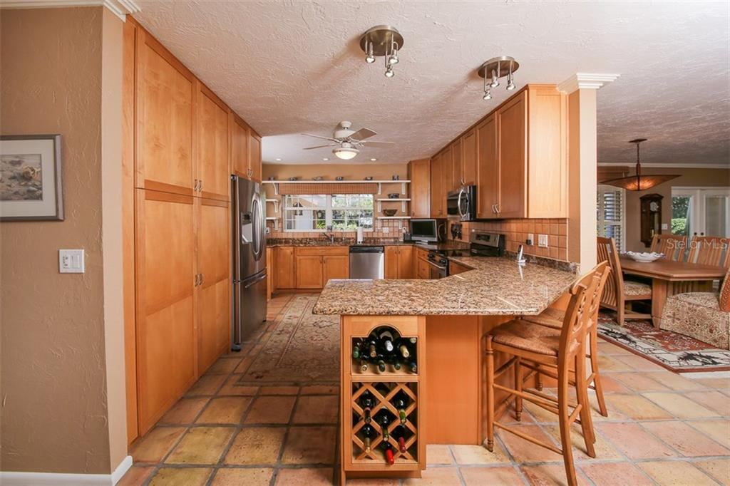Breakfast bar with wine rack open to living and eat in kitchen area. - Single Family Home for sale at 5281 Cape Leyte Way, Sarasota, FL 34242 - MLS Number is A4171478