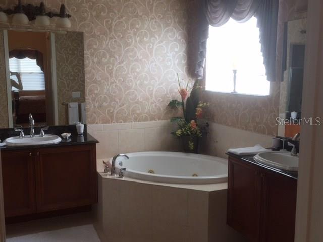 Master Bathroom has separate commode area; Jaccuzi Tub; duel sinks; walk-in shower with marble accents in floor and shower.  Glass block allows in light with maintaining privacy.  Lowered make-up area on the