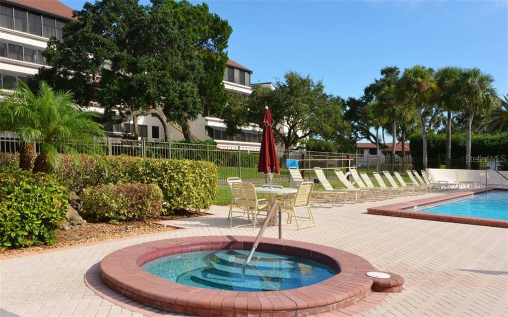 Community swimming pool, spa and paver brick sun deck - Condo for sale at 6263 Midnight Pass Rd #101, Sarasota, FL 34242 - MLS Number is A4182245