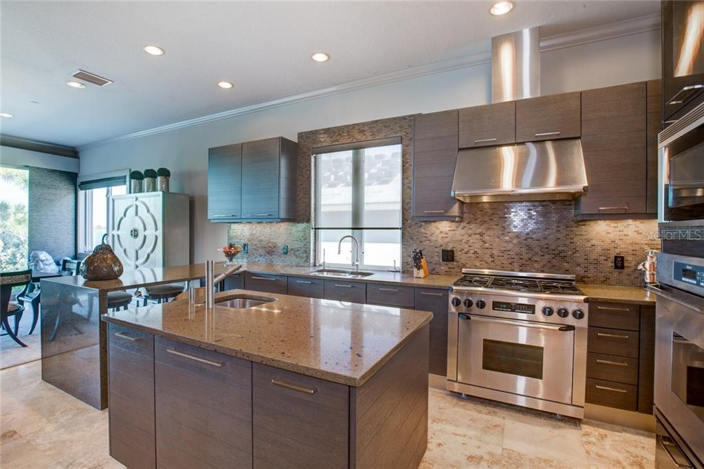 Chef's kitchen w/stainless steel appliances & bar-top seating. - Single Family Home for sale at 8319 Midnight Pass Rd, Sarasota, FL 34242 - MLS Number is A4184004