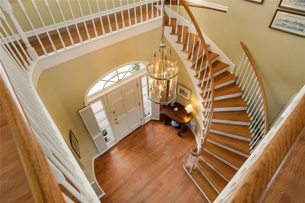 Mesmerizing staircase leading to foyer and front door.  Another staircase leads to guest wing of the home from the downstairs kitchen. - Single Family Home for sale at 3765 Beneva Oaks Blvd, Sarasota, FL 34238 - MLS Number is A4185879
