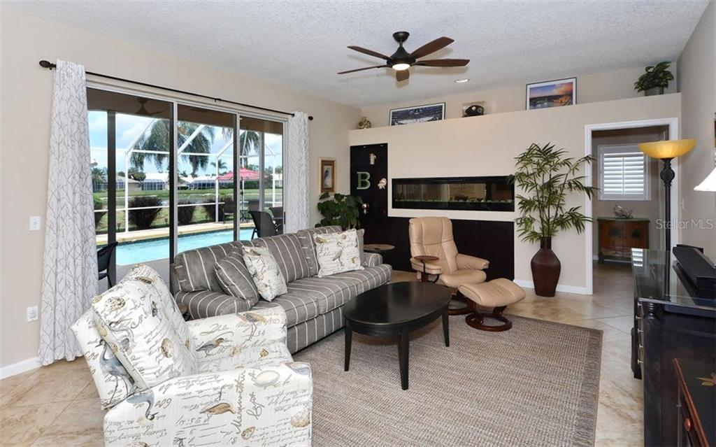 Family room with Dimplex 72 inch electric fireplace. - Single Family Home for sale at 4121 Via Mirada, Sarasota, FL 34238 - MLS Number is A4186485