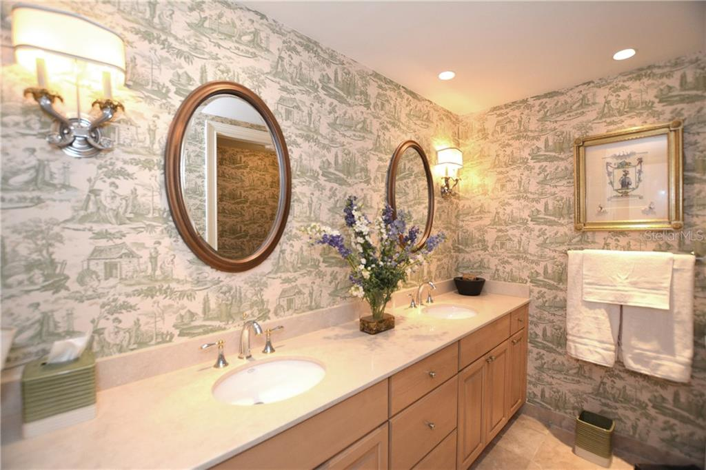 Spacious guest bathroom with dual sinks, wood cabinetry and marble flooring. - Condo for sale at 1111 Ritz Carlton Dr #1505, Sarasota, FL 34236 - MLS Number is A4188921