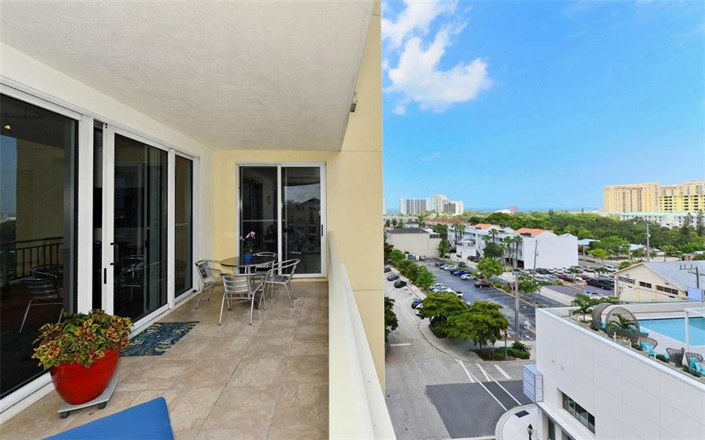 LARGE EXPANSIVE BALCONY, WITH TILED FLOOR. VIEW IS LOOKING OUT TOWARDS THE HYATT AND VAN WEZEL AND THE BAY. YOU CAN SEE VIEWS OF THE BAY FROM THE BALCONY. - Condo for sale at 100 Central Ave #h716, Sarasota, FL 34236 - MLS Number is A4193586
