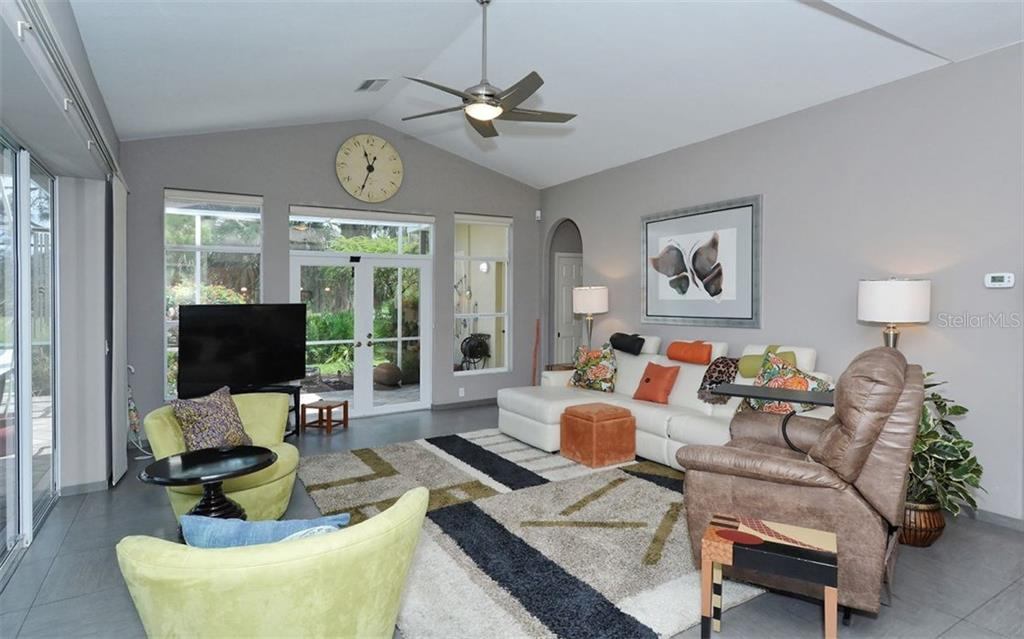 Another view of the bright and light family room. On the right side is entry to the 4th bedroom and full pool bath. - Single Family Home for sale at 8747 Grey Oaks Ave, Sarasota, FL 34238 - MLS Number is A4195019