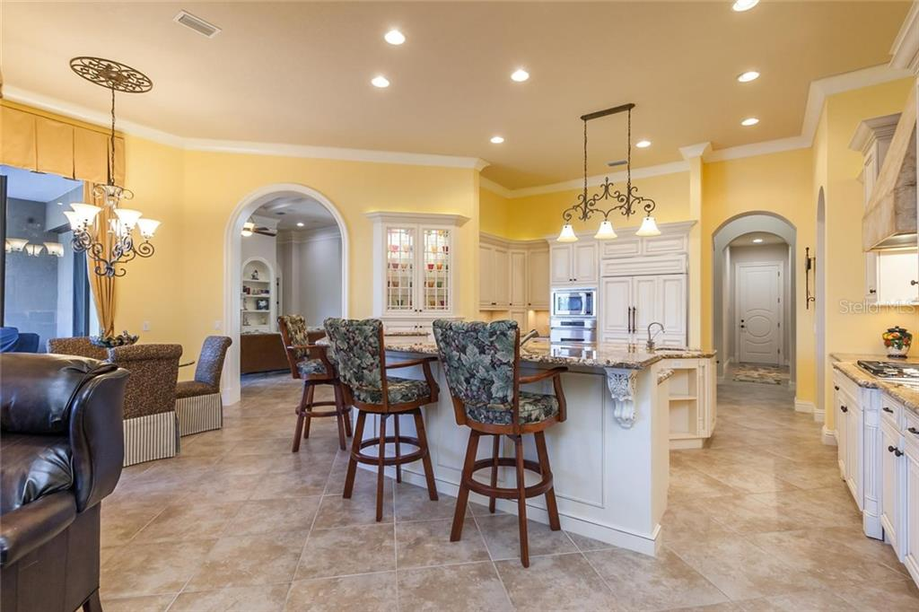 Lovely and Expansive kitchen with large island, breakfast bar seating area, SubZero refrigerator, and five-burner Wolf gas grill. - Single Family Home for sale at 8346 Farington Ct, Bradenton, FL 34202 - MLS Number is A4206244