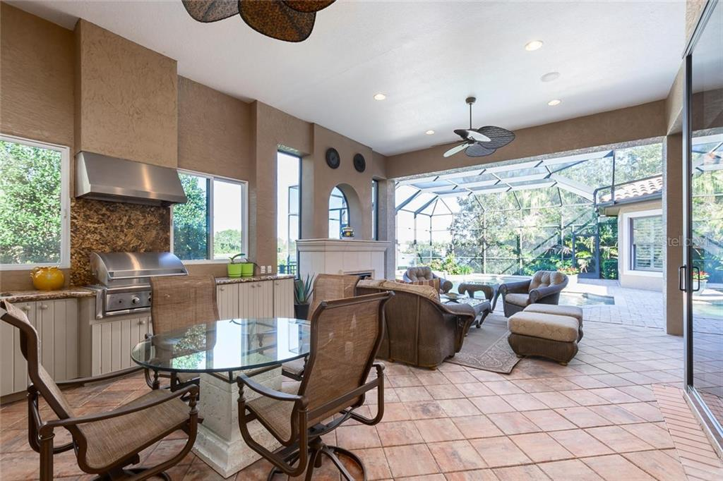 Amazing outdoor summer kitchen with stainless steel gas grill, sink, built-in cabinetry and cozy gas fireplace in seating area. - Single Family Home for sale at 8346 Farington Ct, Bradenton, FL 34202 - MLS Number is A4206244