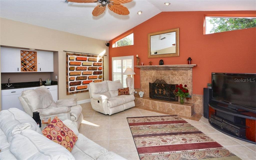 Living room with wood burning fireplace - Single Family Home for sale at 3882 Spyglass Hill Rd, Sarasota, FL 34238 - MLS Number is A4206477