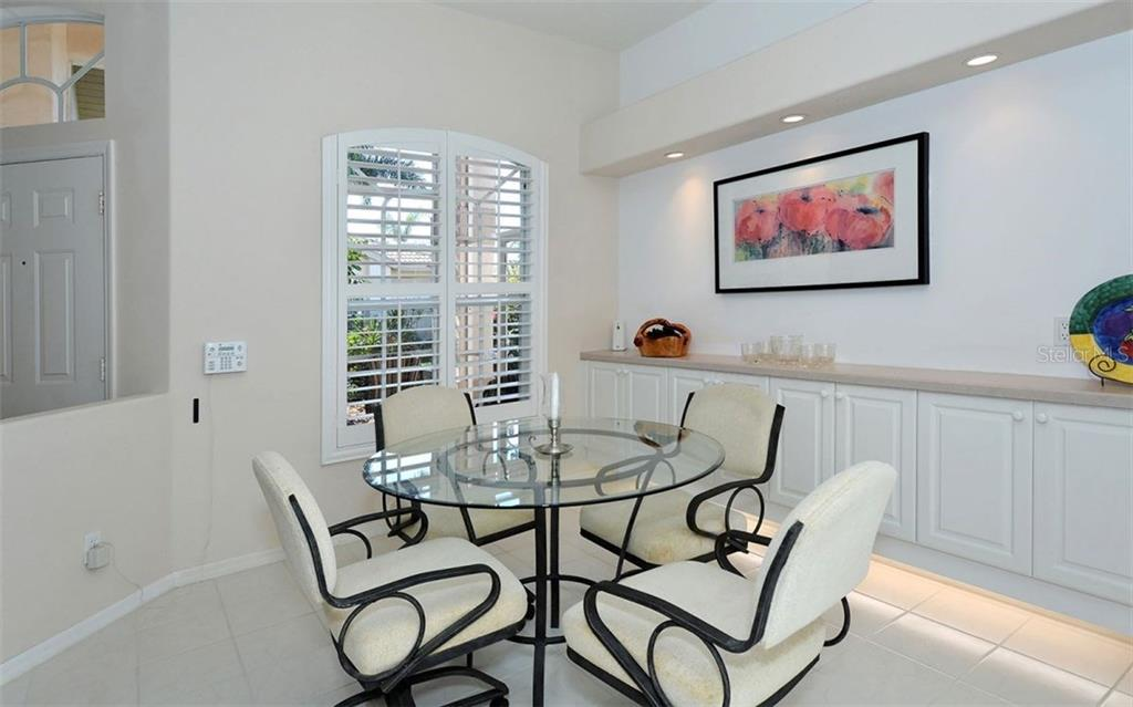 Spacious tiled dinette has raised panel cabinetry with under-lighting, plantation shutters on double windows. - Villa for sale at 9554 Forest Hills Cir, Sarasota, FL 34238 - MLS Number is A4206506