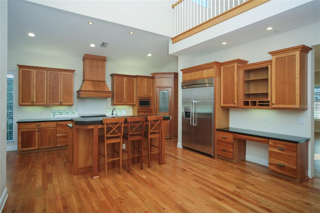 Kitchen with gas appliances, granite, island with breakfast bar, walk in pantry, built in desk. - Single Family Home for sale at 7047 Hawks Harbor Cir, Bradenton, FL 34207 - MLS Number is A4206626