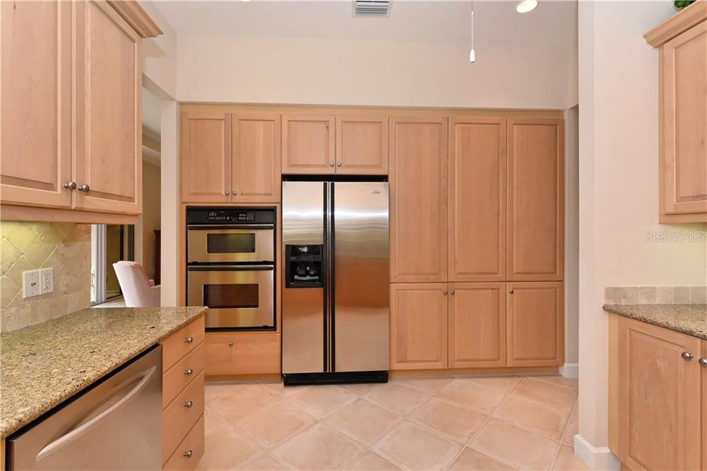 Kitchen view of refrigerator, oven and microwave. - Condo for sale at 5242 Parisienne Pl #201bd30, Sarasota, FL 34238 - MLS Number is A4208770