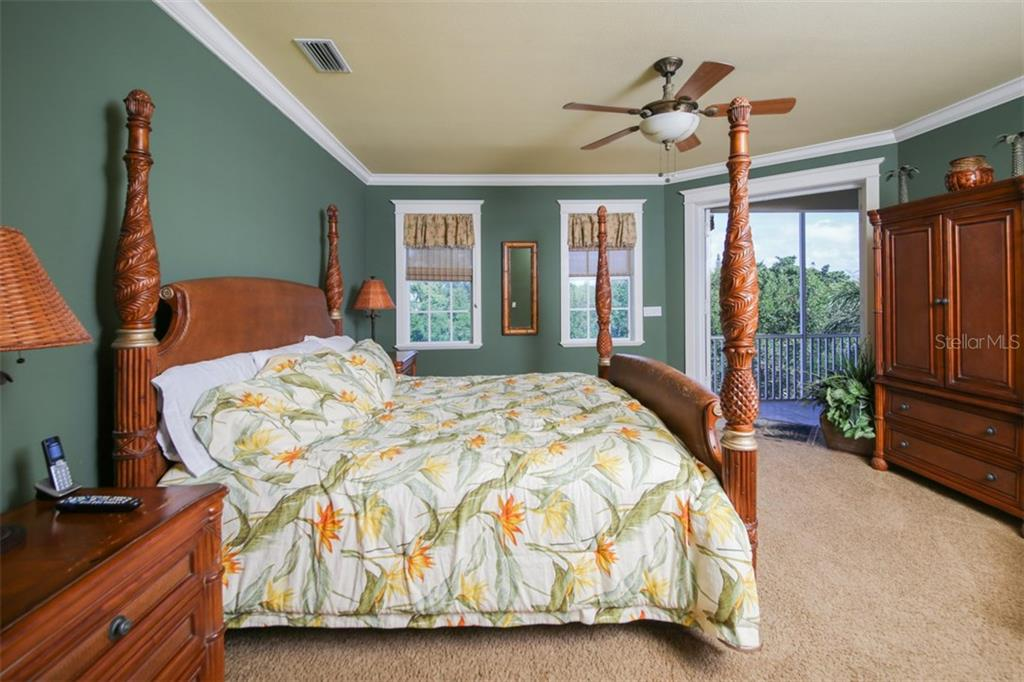 Master bedroom with balcony looking out over pool and canal - Single Family Home for sale at 455 Canal Rd, Sarasota, FL 34242 - MLS Number is A4209817