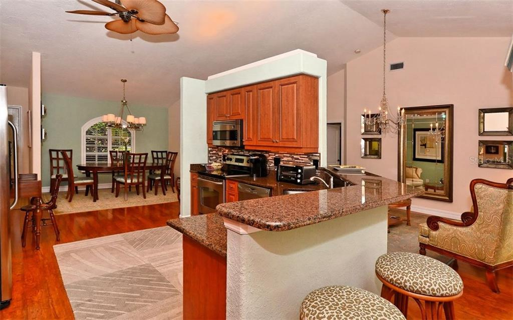 Kitchen to dining room - Single Family Home for sale at 571 Khyber Ln, Venice, FL 34293 - MLS Number is A4210343