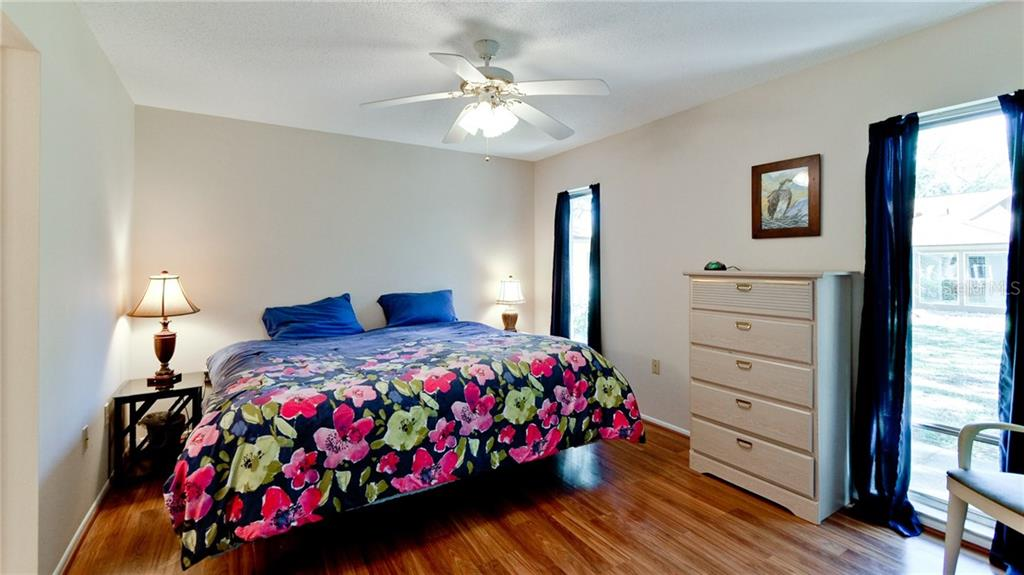 Master bedroom with wood laminate flooring and en-suite bath. - Condo for sale at 5107 29th St W #n/A, Bradenton, FL 34207 - MLS Number is A4213034
