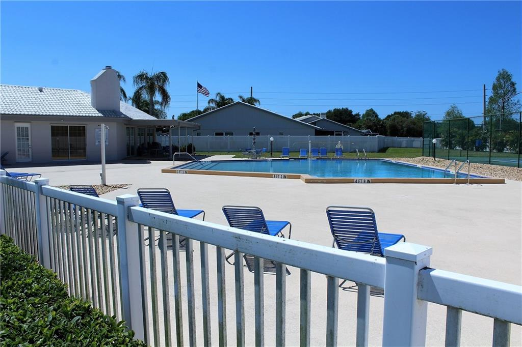 Behind the clubhouse is a large pool big enough for swimming laps and with plenty of deck space for sunning and social gathering. Note the tennis court to the far right. - Villa for sale at 5438 Kelly Dr #12, Sarasota, FL 34233 - MLS Number is A4400319
