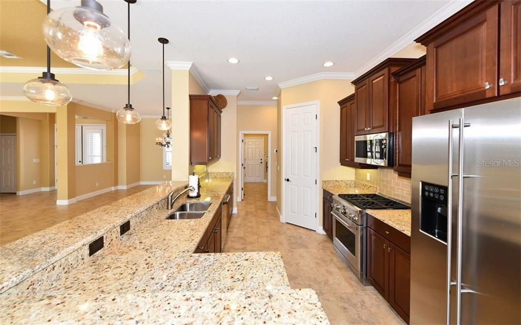 Cook's kitchen with gas range & new top line Monogram appliances. - Single Family Home for sale at 533 Mast Dr, Bradenton, FL 34208 - MLS Number is A4402963