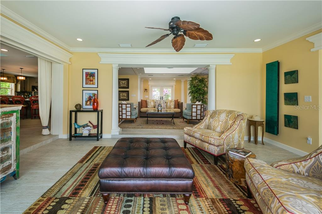 Seating area with hurricane grade sliding glass doors that lead out to the enviable outdoor space. - Single Family Home for sale at 301 Bayview Pkwy, Nokomis, FL 34275 - MLS Number is A4405265