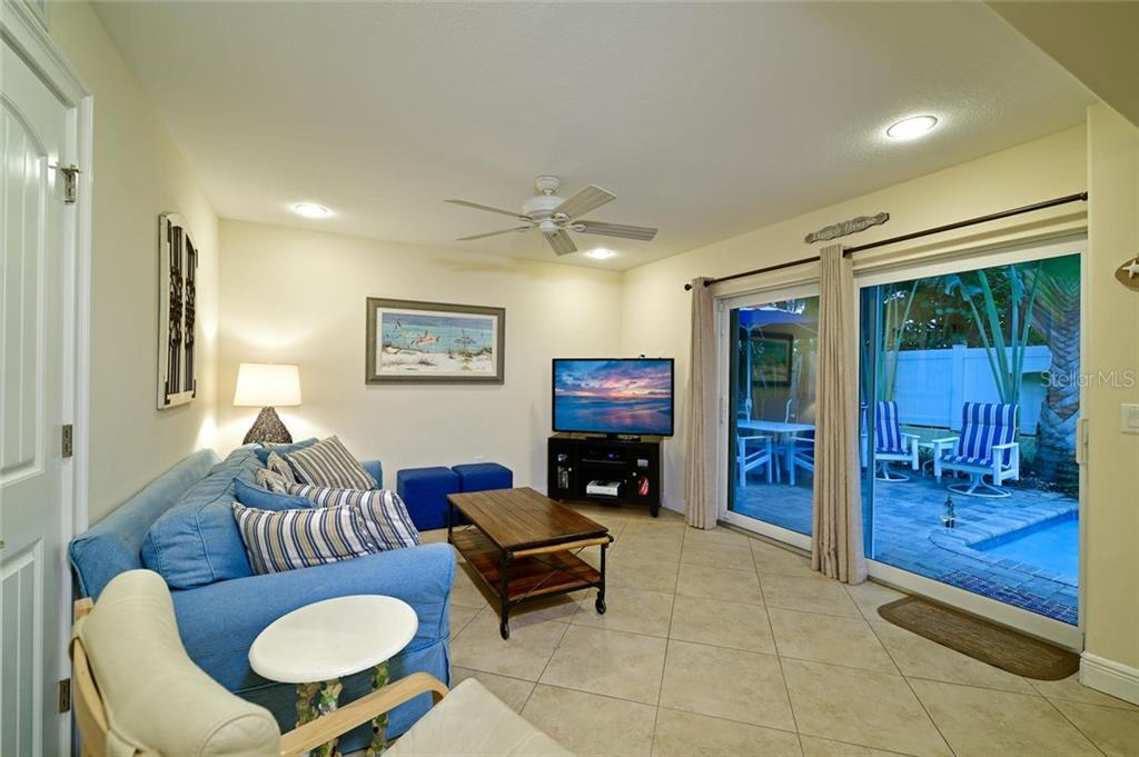 The comfortable living room opens to the patio and pool. - Single Family Home for sale at 113 36th St, Holmes Beach, FL 34217 - MLS Number is A4407267