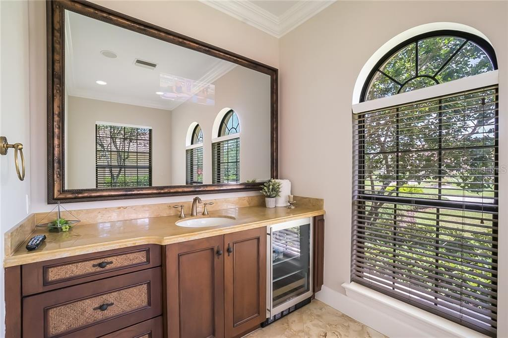 Separate His and Her vanity stations. Notice the mini refrigerator and built-in TV into the vanity mirror - Single Family Home for sale at 7112 Teal Creek Gln, Lakewood Ranch, FL 34202 - MLS Number is A4407645