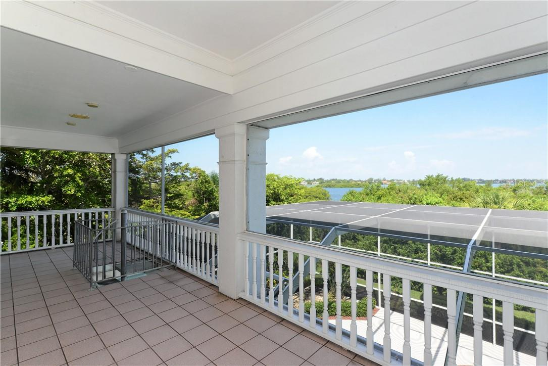 Balcony off the master bedroom with view of the bay and a stairwell going down to the pool area. - Single Family Home for sale at 1427 Cedar Bay Ln, Sarasota, FL 34231 - MLS Number is A4408881