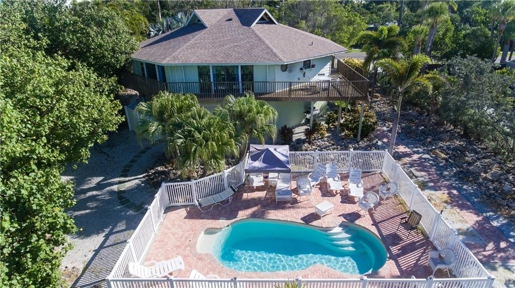 View of home & pool from the west - Single Family Home for sale at 6661 Gulf Of Mexico Dr, Longboat Key, FL 34228 - MLS Number is A4410988