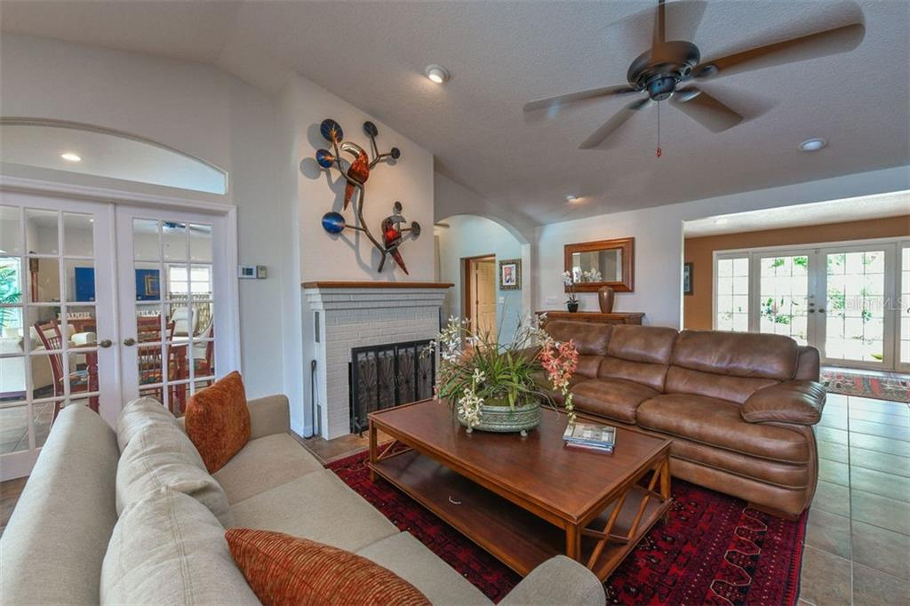 Living room with wood burning fireplace - Single Family Home for sale at 417 Bayview Pkwy, Nokomis, FL 34275 - MLS Number is A4411087