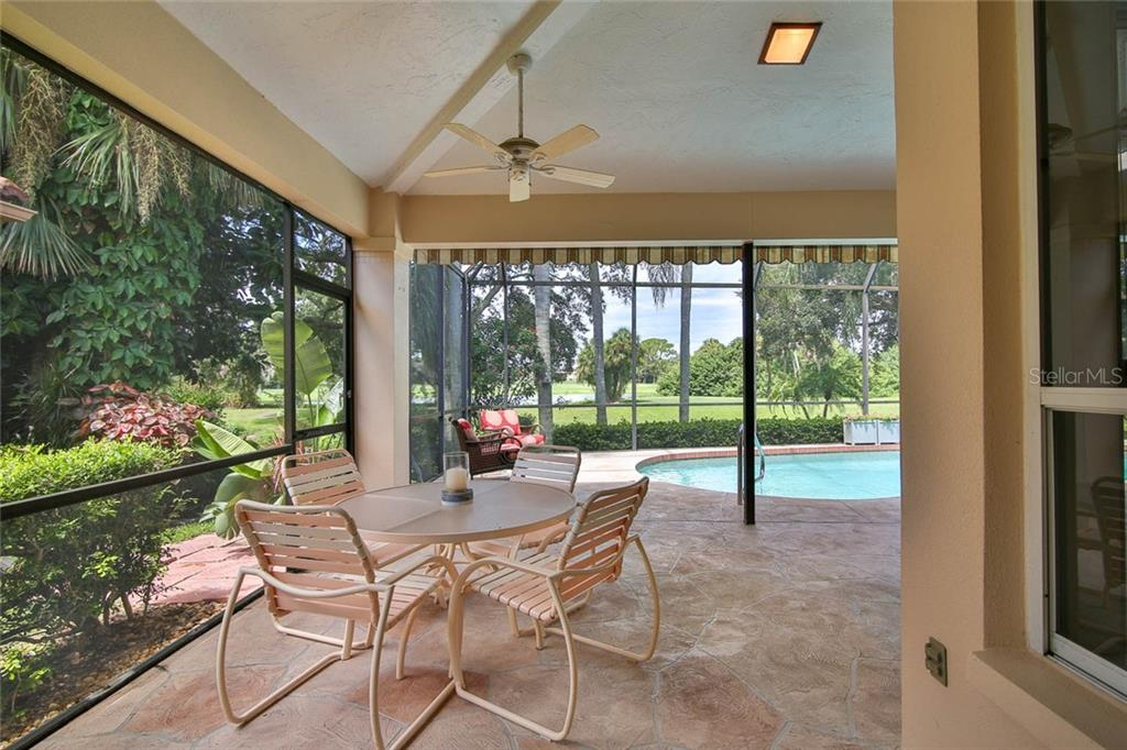 Protected and covered outdoor area for dining, with a gorgeous view of the water features. - Villa for sale at 7686 Calle Facil, Sarasota, FL 34238 - MLS Number is A4413755