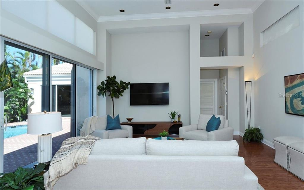From the family room you can access the 2nd bedroom and then through the door at the back right, the garage - Single Family Home for sale at 3529 Fair Oaks Ln, Longboat Key, FL 34228 - MLS Number is A4414992