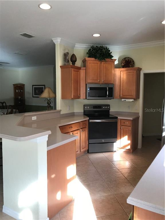 Fully applianced kitchen with breakfast bar, newer appliances and Corian countertops - Villa for sale at 252 Fairway Isles Ln, Bradenton, FL 34212 - MLS Number is A4417217